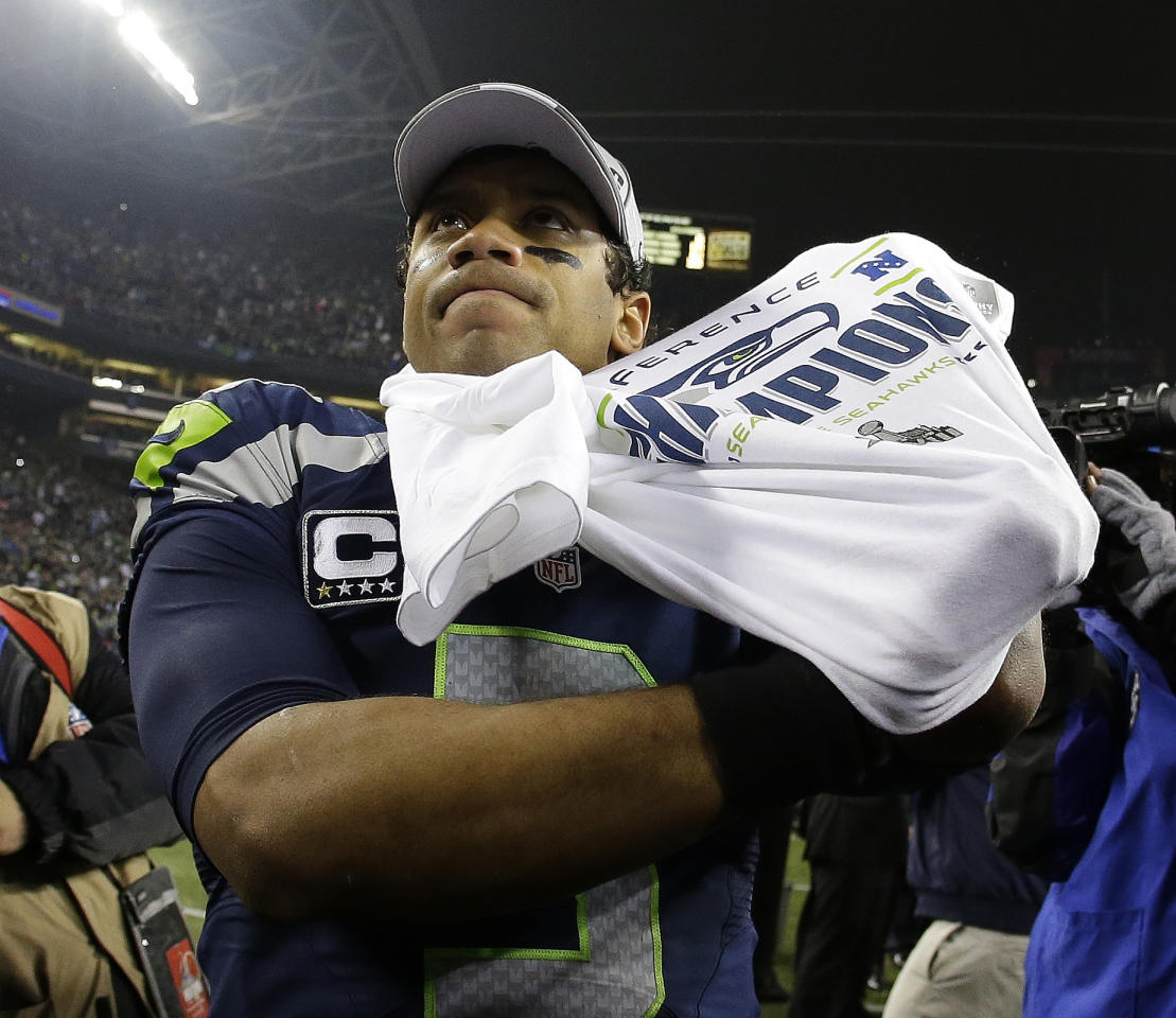 Seattle Seahawks' Russell Wilson puts on a tee shirt after the NFL football NFC Championship game against the San Francisco 49ers Sunday, Jan. 19, 2014, in Seattle. The Seahawks won 23-17 to advance to Super Bowl XLVIII. (AP Photo/Matt Slocum)