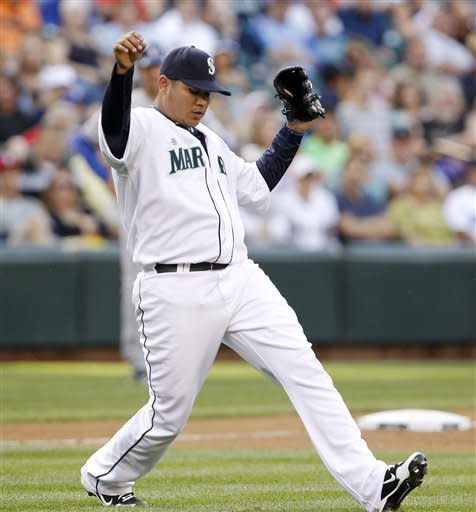 Seattle Mariners starting pitcher Felix Hernandez reacts after throwing out Texas Rangers' Yorvit Torrealba on a grounder during the sixth inning of a baseball game Saturday, July 14, 2012, in Seattle. (AP Photo/Elaine Thompson)