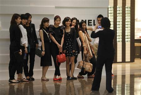 Shoppers pose for a picture in front of a Chanel luxury boutique at the IFC Mall in Shanghai in this June 4, 2012 file photograph. REUTERS/Carlos Barria/Files