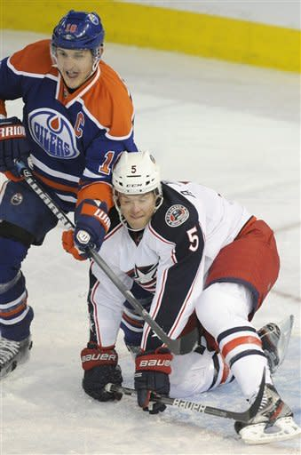 Columbus Blue Jackets Aaron Johnson, right, defends against Edmonton Oilers' Shawn Horcoff during second period NHL action in Edmonton, Alberta, on Wednesday, March 14, 2012. (AP Photo/The Canadian Press, John Ulan)