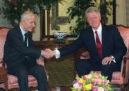 FILE - In this March 26, 2000 file photo, U.S. President Bill Clinton, right, shakes hands with Syrian President Hafez Assad, at the opening of their meeting, in Geneva, Switzerland. On Nov. 13, 1970, Assad a young career air force officer launched a bloodless coup. Fifty years later, Hafez Assad's family still rules Syria. The country is in ruins from a decade of civil war that killed around a half million people, displaced half the population and virtually wiped out the economy. But Hafez's son, Bashar Assad, has an unquestioned grip on what remains. (AP Photo/Laurent Gillieron, File)
