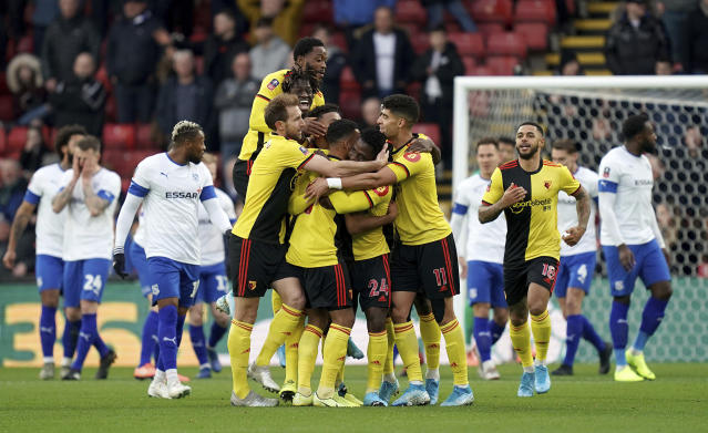 Watford's Tom Dele-Bashiru, center, is mobbed by his team-mates as he celebrates scoring his side's first goal of the game DURING the English FA Cup third round soccer match between Watford and Tranmere Rovers at Vicarage Road, Watford, England, Saturday, Jan. 4, 2020. (John Walton/PA via AP)