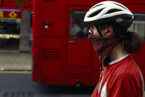 Environment, Pollution, Air, London cyclist wearing scarf tied around nose and mouth to reduce inhalation of pollutants, Red dou