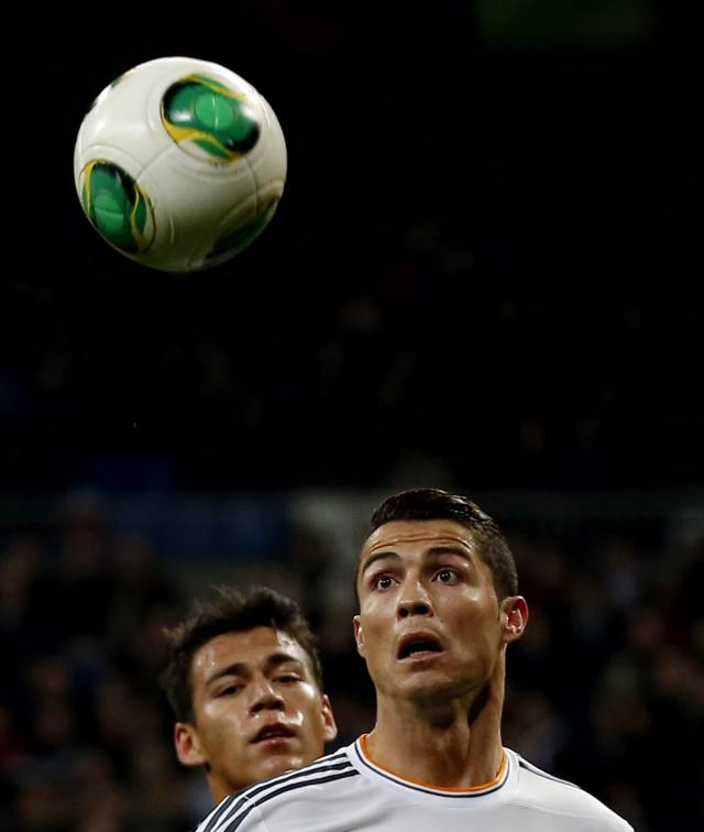 Real Madrid's Cristiano Ronaldo (R) looks at the ball near Espanyol's Hector Moreno during their Spanish King's Cup match at Santiago Bernabeu stadium in Madrid January 28, 2014. REUTERS/Juan Medina (SPAIN - Tags: SPORT SOCCER)