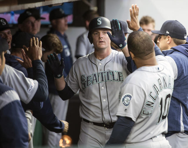 Seattle Mariners' Jay Bruce, center, is greeted by teammate Edwin Encarnacion after hitting a home run off Cleveland Indians starting pitcher Shane Bieber during the fourth inning of a baseball game in Cleveland, Friday, May 3, 2019. (AP Photo/Phil Long)