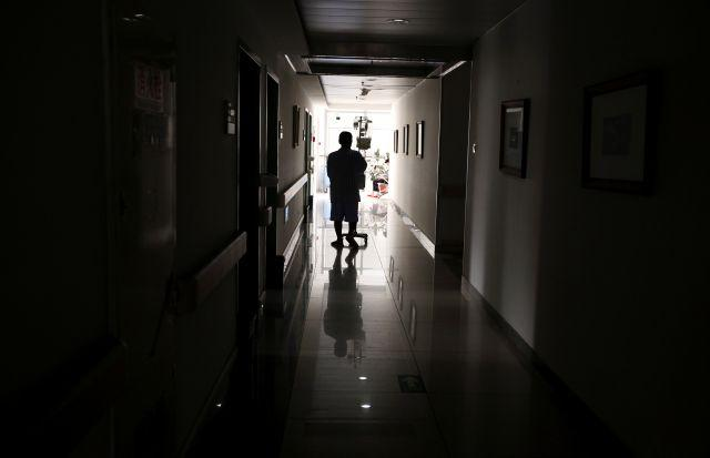 A cancer patient pushes his drip stand as he walks down the hallway of a hospital in Beijing
