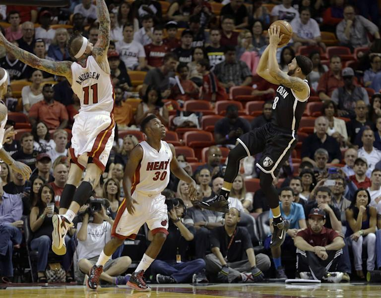 Brooklyn Nets point guard Deron Williams (8) prepares to shoot against Miami Heat point guard Norris Cole (30) and Chris Andersen (11) in the first period of an NBA preseason basketball game, Friday, Oct. 25, 2013, in Miami. (AP Photo/Alan Diaz)