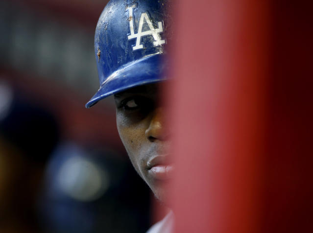 FILE - In this April 12, 2014 file photo, Los Angeles Dodgers' Yasiel Puig peers out from the dugout during the first inning of a baseball game against the Arizona Diamondbacks in Phoenix. Puig fled Cuba on a boat run by smugglers who allegedly made death threats against him and a boxer, according to court documents. The papers describe a dangerous odyssey of shady characters, unpaid debts and violence. (AP Photo/Ralph Freso, File)