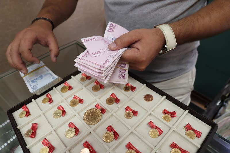 A gold dealer counts Turkish lira banknotes, in Istanbul
