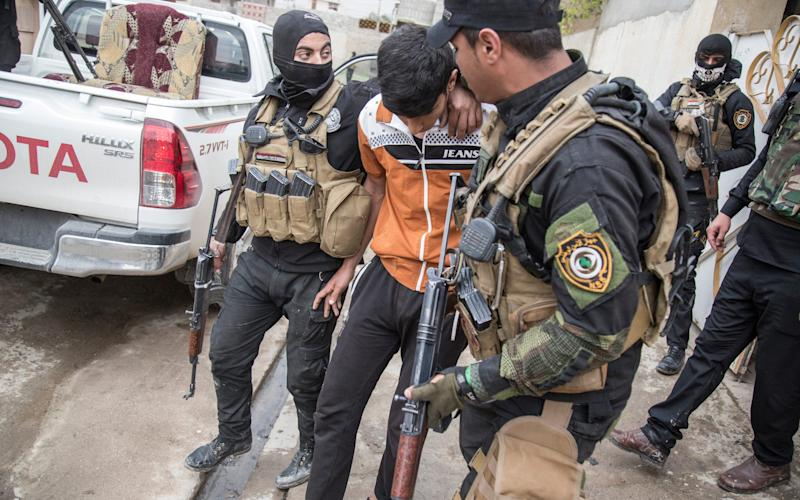 Members of the Iraqi National Security Service arrest a young man they suspect of being affiliated with ISIS - Credit: Sam Tarling