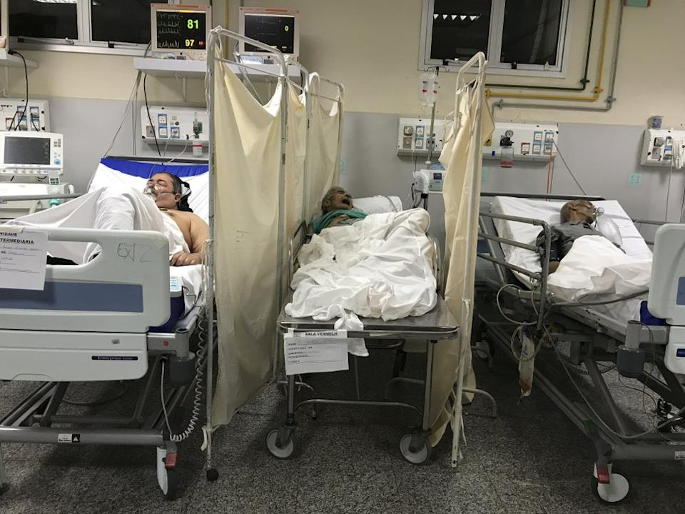 A patient who died from coronavirus, lies on a table between other COVID-19 patients in a room at the Salgado Filho Municipal Hospital in Rio de Janeiro. Source: AP