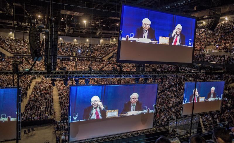 Berkshire Hathaway Chairman and CEO Warren Buffett and his Vice Chairman Charlie Munger in red tie are seen on large screens as they preside over the Berkshire Hathaway shareholders meeting in Omaha Neb. Saturday