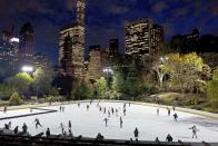 FILE - In this Nov. 3, 2016 file photo, skaters take to the ice at Wollman Rink in New York's Central Park. New York City will terminate business contracts with President Donald Trump after last week's insurrection at the U.S. Capitol, Mayor Bill de Blasio announced Wednesday, Jan. 13, 2021. The Trump Organization is under city contract to operate the two ice rinks and a carousel in Central Park as well as a golf course in the Bronx. (AP Photo/Mark Lennihan, File)