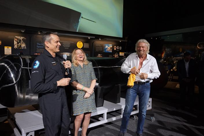 "Richard Branson prepares to don a ""Future Astronaut Training Program"" T-shirt, given to him by Astronaut Mark Stucky (who no longer qualifies as a ""future astronaut""), alongside Ellen Stofan, the director of the National Air and Space Museum. <cite>Chelsea Gohd/Space.com</cite>"