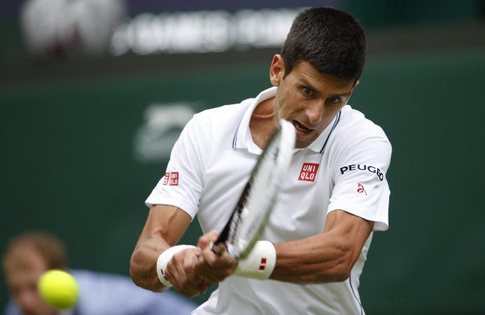 Novak Djokovic of Serbia plays a return to Andrey Golubev of Kazakhstan during their first round match at the All England Lawn Tennis Championships in Wimbledon, London, Monday, June 23, 2014. (AP Photo/Pavel Golovkin)