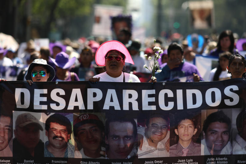 People carry images of people who were disappeared, during a Mother's Day march in Mexico City, Friday, May 10, 2019. Mothers and other relatives of persons gone missing in the fight against drug cartels and organized crime are demanding that authorities locate their loved ones. (AP Photo/Eduardo Verdugo)
