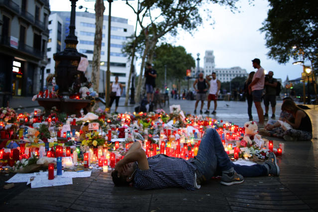 <p>A man lays down next to messages and candles placed after a van attack that killed at least 13, in central Barcelona, Spain, Saturday, Aug. 19, 2017. Police on Friday shot and killed five people carrying bomb belts who were connected to the Barcelona van attack, as the manhunt intensified for the perpetrators of Europe's latest rampage claimed by the Islamic State group. (AP Photo/Manu Fernandez) </p>