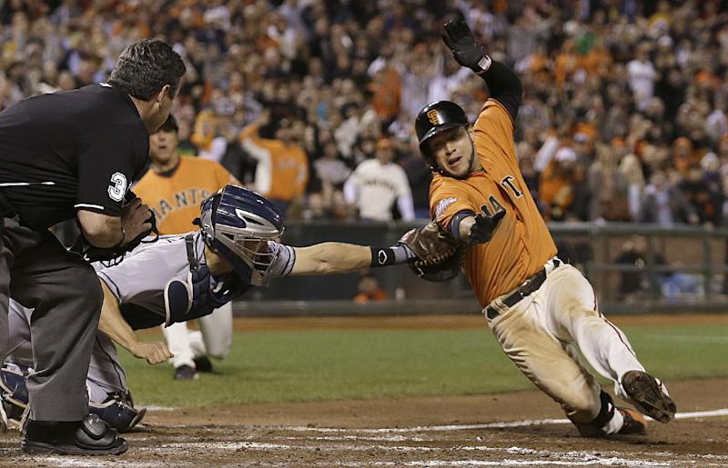 San Diego Padres catcher Nick Hundley, left, tags out San Francisco Giants' Gregor Blanco trying to score after hitting a triple that scored Juan Perez during the eighth inning of a baseball game in San Francisco, Friday, Sept. 27, 2013. Also pictured is home plate umpire Rob Drake. (AP Photo/Jeff Chiu)