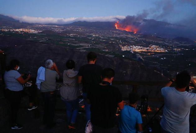 People watch lava flowing after the eruption of a volcano on the Canary Island of La Palma, as seen from Tijarafe, Spain (Photo: REUTERS/Borja Suarez)