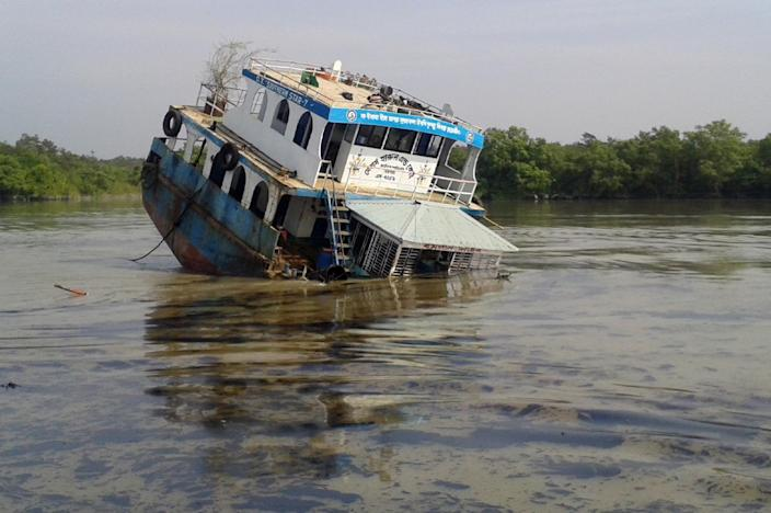 A Bangladeshi oil-tanker lies half-submerged on December 9, 2014, after it was hit by a cargo vessel on the Shela River in the Sundarbans in Mongla (AFP Photo/)
