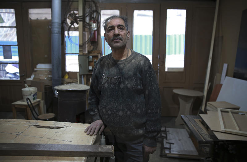 In this Tuesday, Jan. 22, 2019 photo, carpenter Mohammad Reza Tajik is interviewed by The Associated Press about Iran's 1979 Islamic Revolution at his workshop, in northern Tehran, Iran. Forty years after he defected from the shah's Imperial Guard to join the Islamic Revolution, Tajik, like many Iranians from that time, looks back wistfully at the youthful excitement they felt and the losses they suffered since then. (AP Photo/Vahid Salemi)