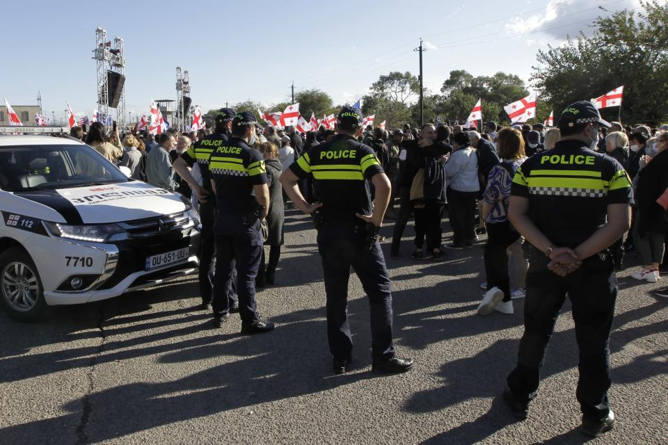 Police block Georgian opposition supporters of former president Mikheil Saakashvili with Georgian national flags during a rally in his support in front of the prison where former president is being held, in Rustavi, about 20 km from the capital Tbilisi, Georgia, Monday, Oct. 4, 2021. Saakashvili was detained in Tbilisi on Saturday, Oct. 1, 2021. Georgia earlier declared Saakashvili wanted as a person convicted in absentia in several criminal cases and treated as a suspect in some others. Georgian authorities have warned repeatedly that he would be detained immediately once over the border. (AP Photo/Shakh Aivazov)