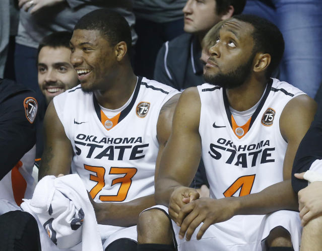 Oklahoma State guard Marcus Smart (33) smiles as he sits on the bench with Brian Williams (4) in the first half of an NCAA college basketball game against Utah Valley in Stillwater, Okla., Tuesday, Nov. 12, 2013. (AP Photo/Sue Ogrocki)
