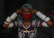 An Indian Lambada tribal woman adjusts her face mask as she stands outside her home in Hyderabad, India, Thursday, May 20, 2021. India has the second-highest coronavirus caseload after the U.S. with more than 25 million confirmed infections. (AP Photo/Mahesh Kumar A.)