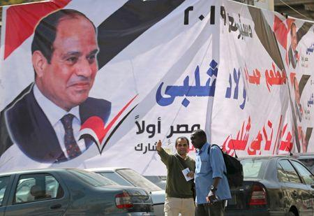 Men stand in front of a banner of the Egyptian President Abdel Fattah al-Sisi before upcoming referendum for the constitutional amendments, in Cairo