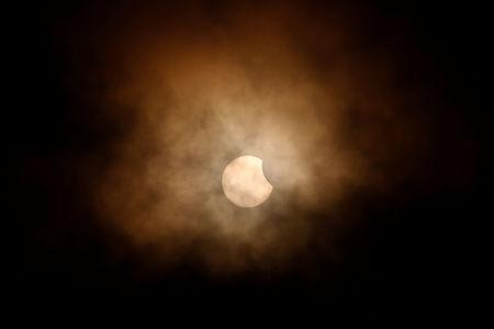 The partial eclipse is obscured by clouds, viewed from the flight deck of the Naval museum ship U.S.S. Yorktown during the Great American Eclipse in Mount Pleasant, South Carolina. REUTERS/Randall Hill