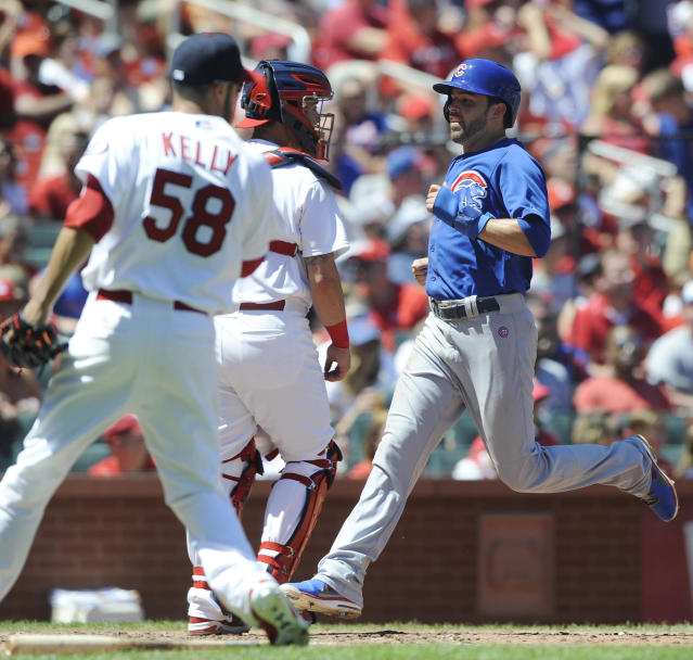 Chicago Cubs' David DeJesus, right, scores on an error by St. Louis Cardinals' Matt Holliday as Cardinals' Joe Kelly (58) and Tony Cruz, center, look on in the third inning in a baseball game on Sunday, Aug. 11, 2013, at Busch Stadium in St. Louis. (AP Photo/Bill Boyce)