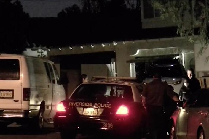 Police officers investigate the scene where a woman's body was found stuffed in a refrigerator.