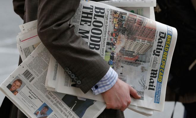 A man carries newspapers in London on April 16.