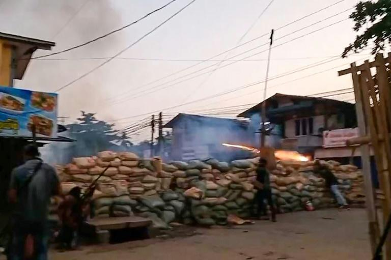 A screengrab from Hantarwadi Media video shows a protester setting off fireworks from behind a makeshift barricade while a man holds a homemade rifle during the clashes in Bago