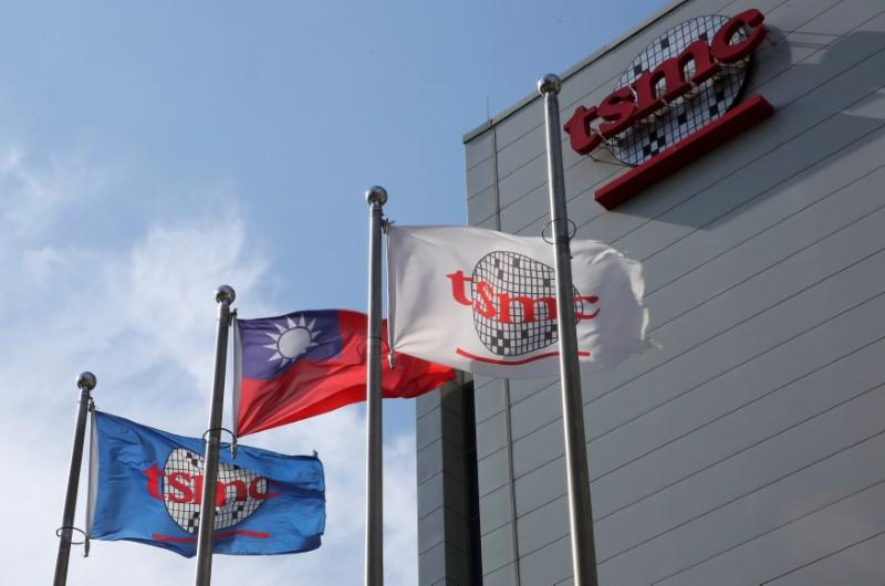FILE PHOTO: Flags of Taiwan and Taiwan Semiconductor Manufacturing Co (TSMC) are displayed next to its headquarters in Hsinchu