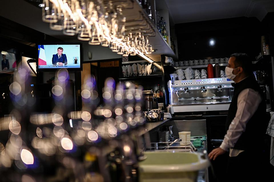 A barman in Marseille watches Macron's press conference on Wednesday evening - getty