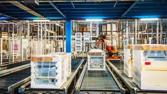 Household appliance assembly line with a conveyor belt and automated robotic arms.