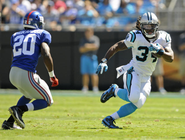 Carolina Panthers running back DeAngelo Williams (34) tries to run past New York Giants cornerback Prince Amukamara (20) during the first half of an NFL football game in Charlotte, N.C., Sunday, Sept. 22, 2013. (AP Photo/Mike McCarn)