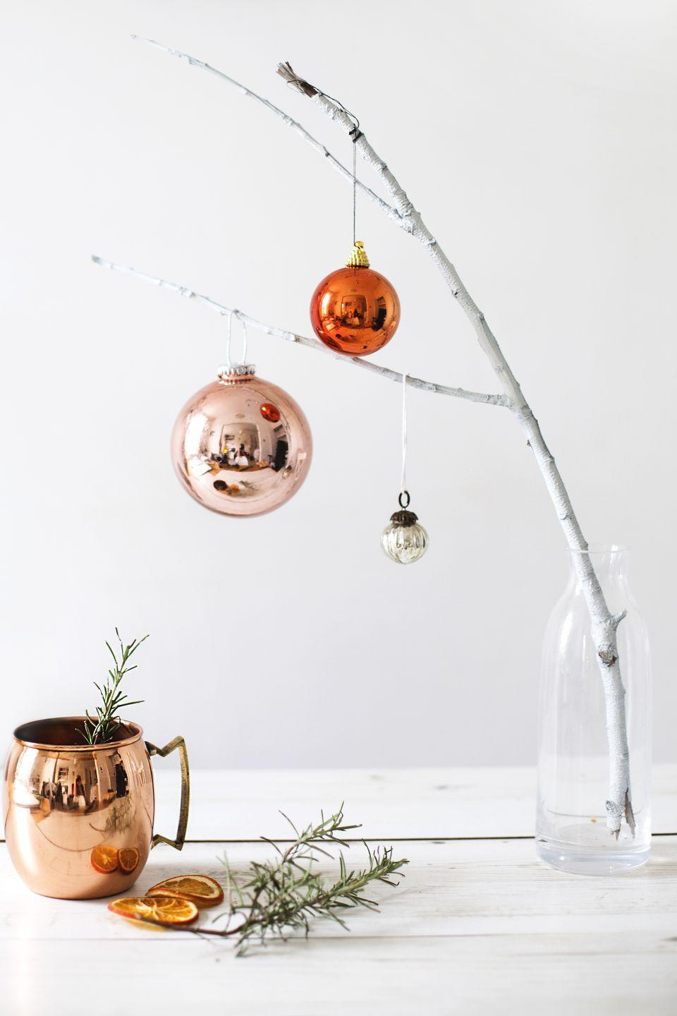 "<p>This adorable ""tree"" will look chic on any surface around your home, and it's stupid easy to make. Just find a sturdy tree branch, apply spray paint, set it in a small glass bottle or vase, and decorate!</p><p>Get the tutorial at <a href=""https://thelovelydrawer.com/styling-the-seasons-december-2/"" rel=""nofollow noopener"" target=""_blank"" data-ylk=""slk:The Lovely Drawer"" class=""link rapid-noclick-resp"">The Lovely Drawer</a>.</p>"