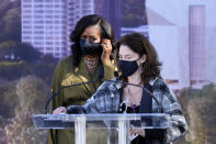 Michelle Breger sanitizes the podium after the previous speaker, as former first lady Michelle Obama approaches it to speak during a groundbreaking ceremony for the Obama Presidential Center Tuesday, Sept. 28, 2021, in Chicago. (AP Photo/Charles Rex Arbogast)