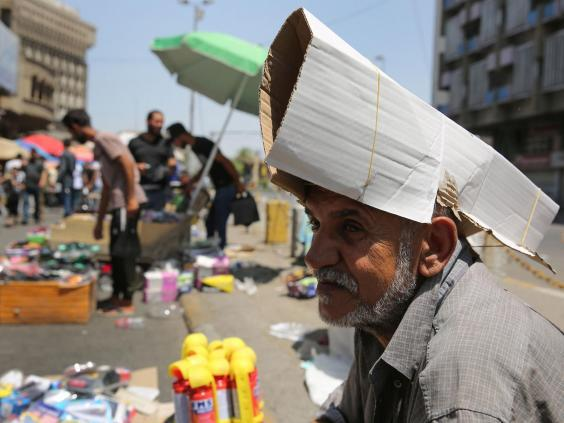 An Iraqi street vendor protects his head from the sun by using a piece of cardboard (AFP/Getty Images)