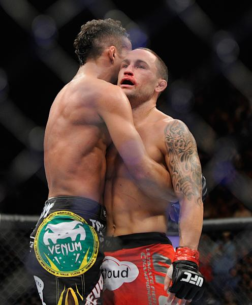 Frankie Edgar, right. is hugged by Charles Oliveira after their UFC 162 mixed martial arts featherweight bout at the MGM Grand Garden Arena on Saturday, July 6, 2013, in Las Vegas. Edgar won the fight by an unanimous decision. (AP Photo/David Becker)