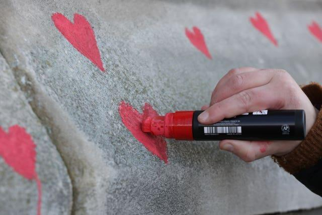 Members of bereaved families painted red hearts on the memorial