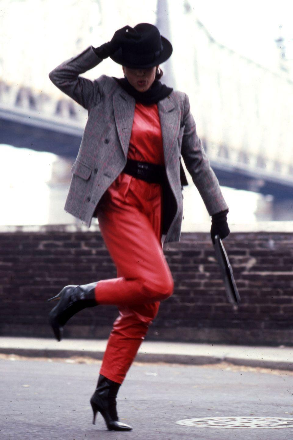 <p>A model wears a red jumpsuit, gray blazer, and black hat for photographs in front of a bridge in New York.</p>
