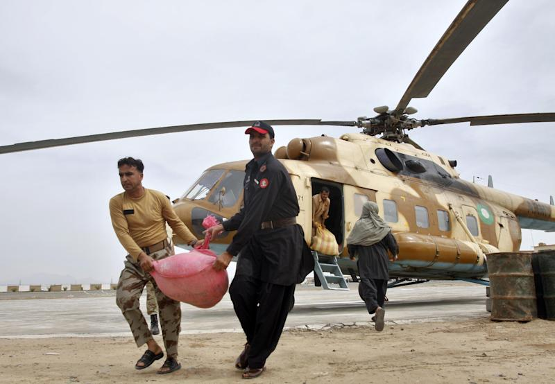 Pakistani paramilitary soldiers unload food stuff from an army helicopter to send them into earthquake hit area, at a military base in Dalbandin, a town of Pakistan's southwestern Baluchistan province, Wednesday, April 17, 2013. Hundreds of Pakistani soldiers joined the effort to rescue victims of a deadly earthquake near the Iranian border, evacuating 16 of the more seriously injured by helicopter, the military said Wednesday. (AP Photo/Arshad Butt)