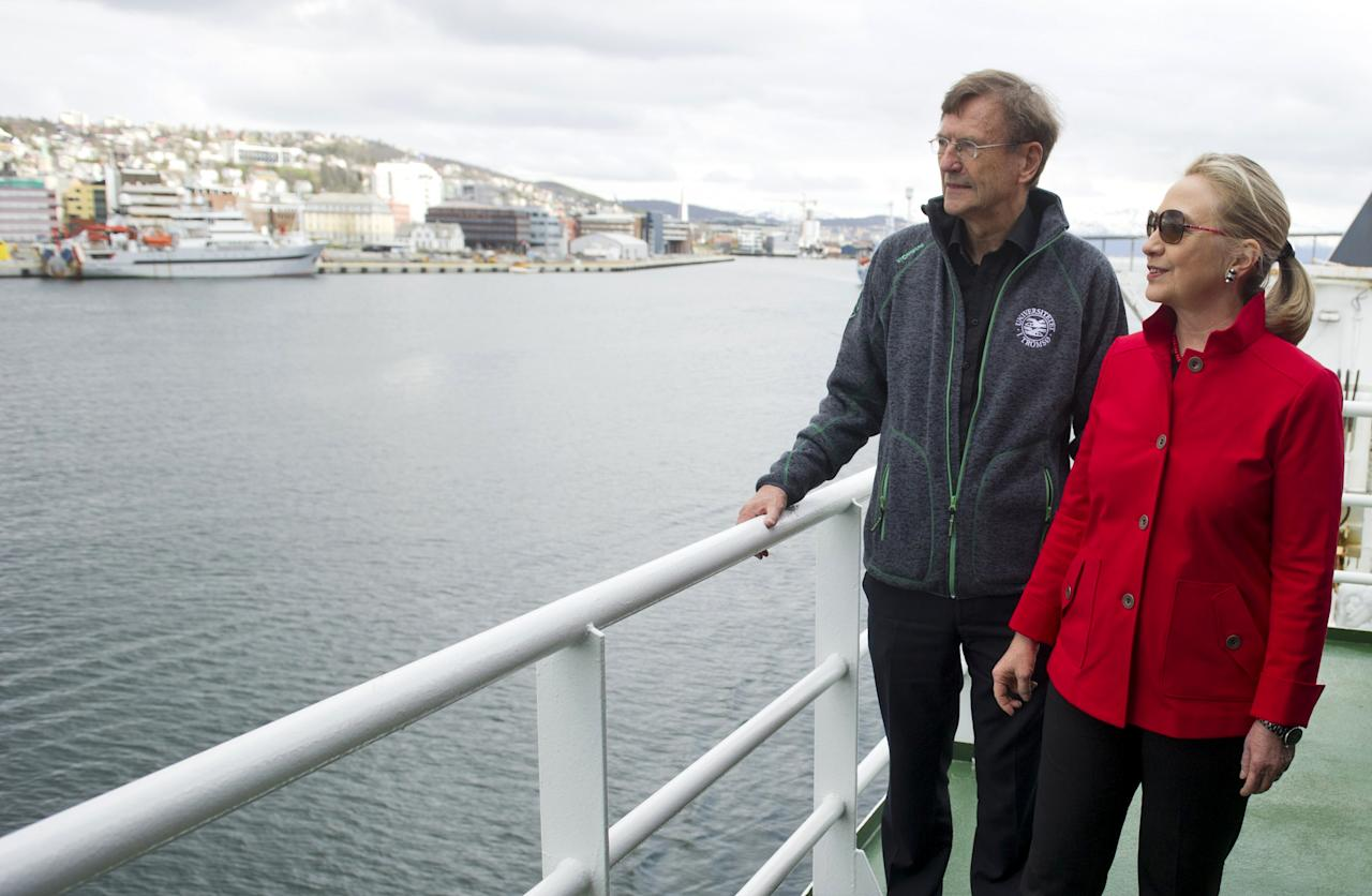 US Secretary of State Hillary Rodham Clinton, right, speaks with Jarle Aarbakke, Rector of the University of Tromso, aboard the Arctic Research Vessel Helmer Hanssen during a boat tour of the coastline with Norway's Minister of Foreign Affairs Jonas Gahr Stoere, unseen, off the coast of Tromso, Norway, Saturday June 2, 2012. (AP Photo/Saul Loeb, Pool)