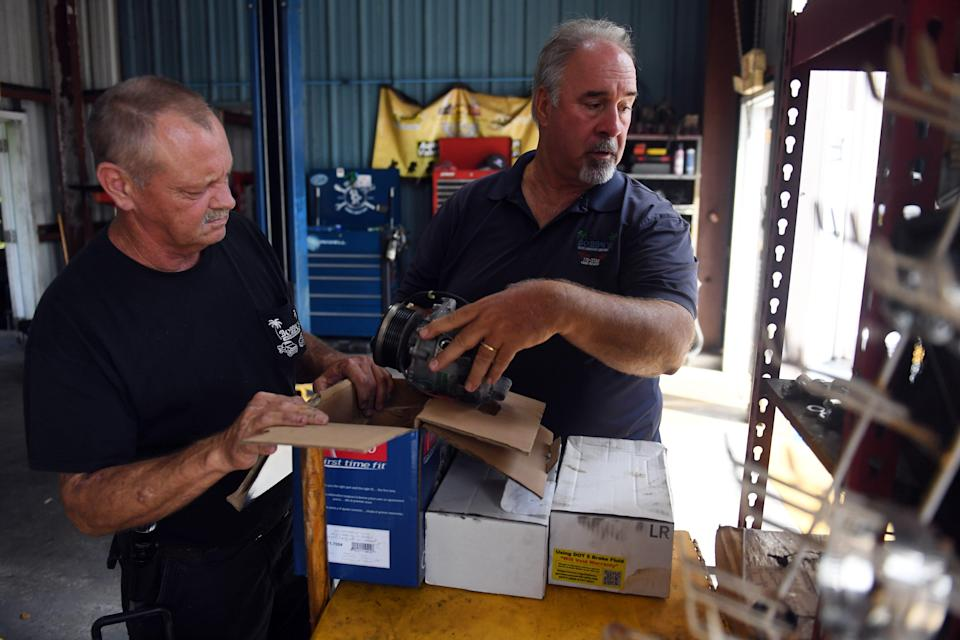 Bobby Ford (right) talks with longtime employee Dickey Millard in the service bay of Ford's shop, Bobby's Auto Service Center, on Wednesday, Sept. 1, 2021, in Vero Beach. Both Ford and his twin brother, Billy, became sick with coronavirus. But Ford was vaccinated while his brother was not. Billy Ford died Aug. 14, leaving behind a wife, three children, his mother and three brothers.