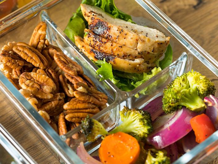A meal prep container on a wooden table with nuts, chicken, and veggies