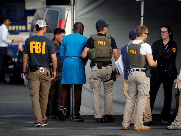PHOTO: Federal agents hold a detainee after predawn raids that saw dozens of people arrested, Aug. 22, 2019, in Los Angeles. 80 people were charged with participating in a conspiracy to steal millions through a range of fraud schemes and money laundering. (Reed Saxon/AP)