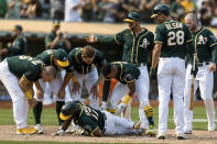 Oakland Athletics teammates attend to Elvis Andrus, center, as he collapsed with an injury after scoring against the Houston Astros in the ninth inning of a baseball game in Oakland, Calif., Saturday, Sept. 25, 2021. The Athletics won 2-1. (AP Photo/John Hefti)